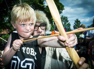 Filip Mattsson från Brödraskapet Gillet instruerar sexårige Adam Persson i bågskyttets konst.
