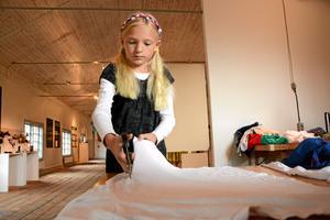 Klipper till. Vera Hillius skulle klippa till en väst av en gammal vit T-tröja. Det var ett av de tio förslagen på vad man kunde använda just gamla T-shirtar till som deltagarna fick prova på under gårdagens workshop på pappersbruksmuseet.Foto: Adam Söder
