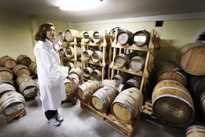 Kristina Anerfält Jansson med whiskyfaten som ligger under logen. Här växlar temperaturen med årstiderna och bidrar till smaken på whiskyn.
