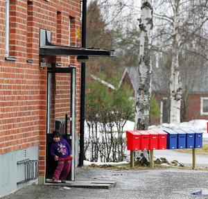 Femåriga Gabriella tittar ut från porten i sin nya bostad.