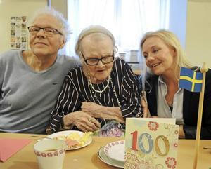 100-årsjubilaren Gudrun Johansson, mitten, lät sig väl smaka av såväl kaffe som tårta och gladdes extra åt att sonen Håkan Johansson och barnbarnet Charlotte Johansson fanns på plats som lite extra stöd bland alla hurrarop.