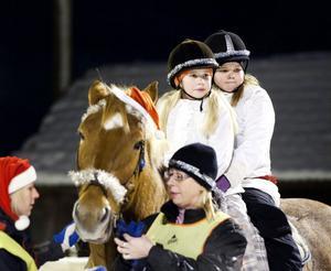 Isabelle Karlsson och Molly Hjort passade på att rida samtidigt på hästen Noppe under luciatåget genom Norr Amsberg.
