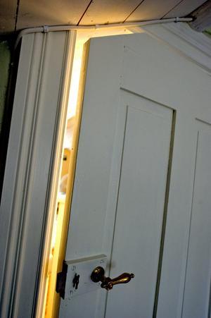 Det är riktigt lågt i tak på övervåningen. Den här dörren, som satt på bottenvåningen, har sågats av både på höjden och i ett hörn. Den utanpåliggande låskistan sparades förstås.
