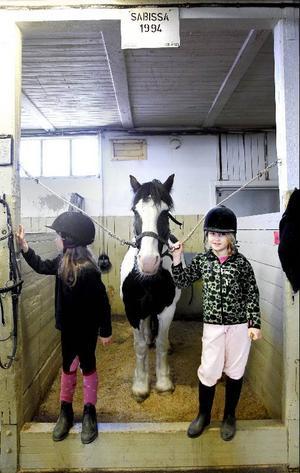 Halva nöjet på ridskolan är att pyssla om hästarna i stallet. Sjuåriga Matilda Persson och Linnéa Gisslén, åtta år, går i samma klass på Norra skolan. På fritiden möts de också här hos hästen Sabissa.