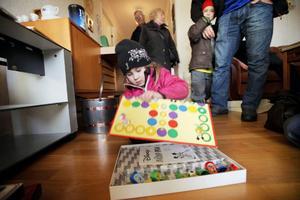 """Lemonie Söderberg, 4, var med brorsan Melwin, 6, som skymtar i bakgrunden samt pappa och mamma för att leta efter spel på auktionen. Och de hittade ett fint. """"Titta, spelreglerna är kvar"""", utbrast Lemonie. Spelet fick de för en tjuga."""