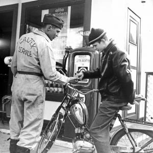Ett foto som, visar Sigge Bröms, legendarisk hockeyspelare i leksands IF, när han tar betalt av en mopedist som tankat vid Caltexmacken där Bröms arbetade.