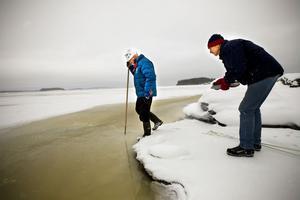 Sten Skalman varnar skridskoåkaren Gösta Enström för att ge sig ut för långt. Några hundra meter ut från stranden vid Batteriudden har oljeansamlingarna bildat förrädiska råkor.