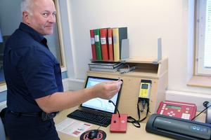 Peter Nystedt, räddningschef på räddningstjänsten, visar hur tutorna sätts igång med hjälp av en nyckel. På skärmen finns en karta över Ljusdals alla tyfoner.