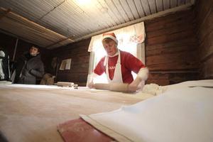 Gunvor Persson kavlar ut tunnbröd. De blir rund sju bröd per liter deg. Runt 26 liter har de knådat ihop.