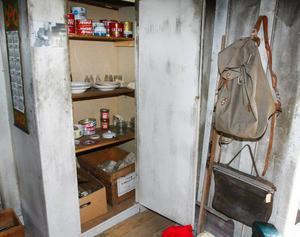 I skafferiet finns gamla fina burkar bevarade som till exempel Jojka renköttbullar på översta hyllan. Vid sidan om hänger den ryggsäck han bland annat bar när han var ner till Strömsund för att handla.