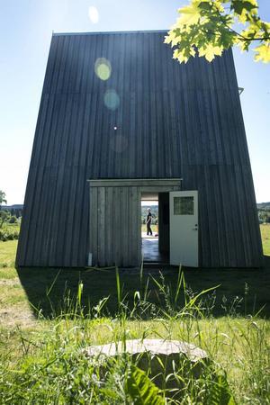 """Huset har inga fönster på """"baksidan"""" utan vänder ryggen mot skogen. Endast entrédörren gör huset välkomnande från denna sida."""
