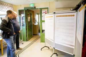 Erik Andersson och Lars Björk läser på informationstavlan som är uppsatt på biblioteket.