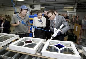 Året är 2011 och Patrik Ahlberg visar hur man limmar fönster på fönsterfabriken i Lingbo. Både prins Daniel och kronprinsessan Victoria fick testa, med blandade framgångar. Bild: Arkiv