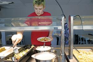 Jerry Larsson lägger på mat på sin tallrik.