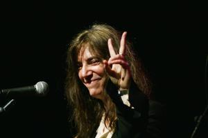 2006. Patti Smith gör fredstecknet till publiken under sitt uppträdande.