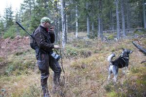 Oskar Åsåker kommunicerar till de övriga innan han släpper hunden.