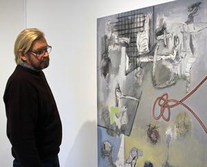 Tapani Björkbacka betraktar en av sina målningar.