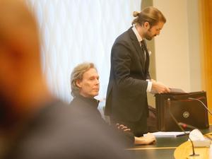 Gryningspyromanen Ulf Borgström under fredagens häktningsförhandling i Västmanlands tingsrätt. Stående bredvid honom syns hans försvarare Viktor Svartz.