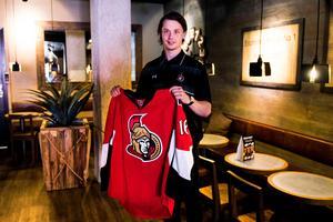 Jonathan Dahlén håller upp den Ottawa-tröja han fick under draften år 2016.