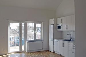 En två på övervåningen med högt tak, balkong och köksutrustning i vitt.