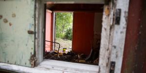 Precis vid Yngern står ett förfallet uthus fullt av skräp, på trappan ett bilbatteri.