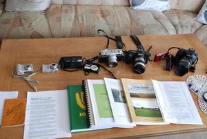 Att skriva och fotografera är två av Görans stora intressen. Här finns en samling kameror och de böcker och häften som han medverkat till att skriva.