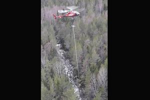 Helikoptern med gripklo kapar och lyfter bort tre träd på två minuter, sammanlagt cirka 150 träd per dag. Foto: Kenneth Stefansson, Vattenfall