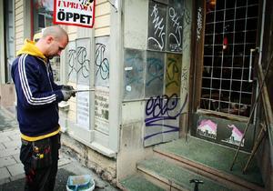 Pether Espemo lagar fönstret till dörren. Under natten till måndagen upptäckte Signe Olofsson att någon kastat in en sten genom dörrutan till hennes kiosk.