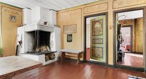 I vardagsrummet märks de handmålade vägg- och dörrdetaljer som säljarnas farfar målat.