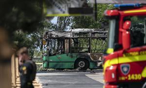 En utbränd buss står kvar på gatan i väntan på att gasflaskorna skall svalna. Foto: Johan Nilsson/TT