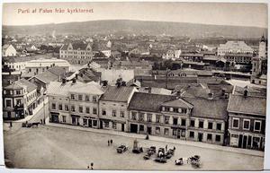 Parti af Falun från kyrktornet. Ett av många vykort med motiv över Stora Torget. Här syns både hästdroskor och motoriserade droskor. Carl Björklunds bokhandel ligger tre butiker in från Falugatan, och gav även ut vykortet.