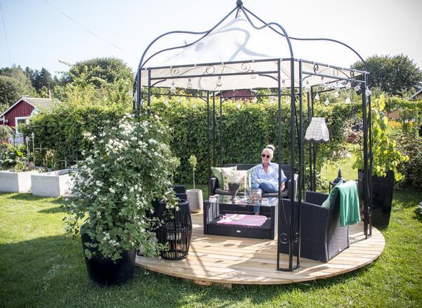 Den blomstrande trädgården utgör ett ljuvligt vardagsrum. I trädgården har Anna placerat en paviljong inredd med sittmöbler, lampor och växter.