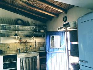 Köket har bland annat ett snyggt blått kylskåp från Smeg som matchar husets blå knutar och dörrar. Foto: Maud Frykberg
