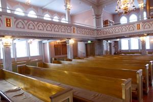 I kyrkorummet finns läktare på tre sidor, väggarna är klädda med pärlspånt och målade i nyanser av grått och rosa. Foto Seved Johansson