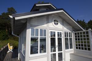Huset är vitt med gråa detaljer och har ett svart tak.