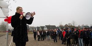 Rektorn Jessica Ambjörn skålar in planen med eleverna inför första fotbollsmatchen på det nya grusunderlaget.