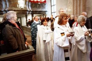 """Ett 100-tal personer hade kommit för att se när Ragnar Persenius, biskop i Uppsala stift, välkomnande Anita Jonsson som församlingens nya """"andlige ledare""""."""