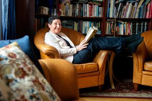 Harriet Pettersson har inrett sin lägenhet efter årstider och färger. Här i vinterrummet i favoritfåtöljen med en bok i handen.  Foto: Annika Persson