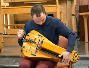 Johannes Geworkian Hellman stämmer sin vevlira. Det hade varit intressant att få veta mer om instrumentet under konserten.