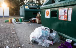 En säck med plastförpackningar har lämnats på marken, istället för att tömmas i containern.