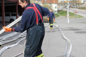 Peter Winberg och Jakob Lindsmyr hjälptes åt att återställa och samla ihop de vattenslangar som hade använts under släckningen.