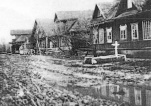 Aropakkasi, Eric Westers pappas hemby. Fotot är taget år 1944, strax innan byn brändes ner av tyskarna. Bygatan är sönderkörd efter en tyskt reträtt, och vid huset längst till höger i bild, en tysk officersgrav. Eric Westers familjs hus är huset med vitt staket. Foto: Privat