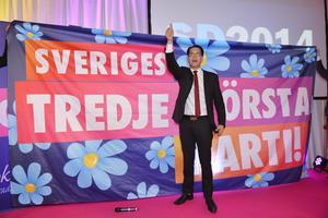 Sverigedemokraternas partiledare Jimmie Åkesson framför en banderoll med texten