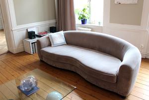 Soffa med rund form och en glasskiva som vävar på marmorklot.