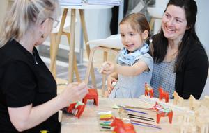 Kerstin Reuterborg från Nils Olssons Dalahästtillverkning målar dalahästar med säker hand medan fyraåriga Theresa Kecker och mamma Dorothea imponerat ser på.Foto: Thomas Kolbein Bjørk Olsen