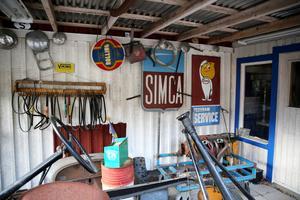 En salig blandning av gamla skyltar och verktyg utanför macken.