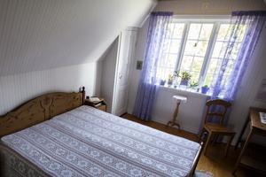 På övervåningen finns ett gästrum där inredningen går i en ton av lila.