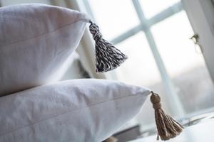 Linne blir kuddar. När Karin syr om återvunna textilier lägger hon gärna till någon ny detalj, som tofsar eller bollfrans.