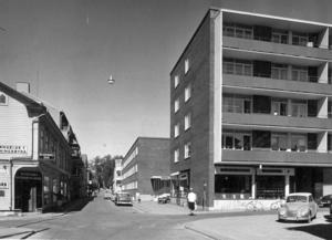 Sommaren 1963. Flerbostadshus i kvarteret Pastorn, som ligger vid Brogränd-Prästgatan-Färjemansgränd-Kyrkgatan. Fotot visar byggnaden från Prästgatan 5-9 (i dag hotellkedjan Clarion) färdig till nyåret 1962. Gatan som syns framför byggnaden och som korsar Prästgatan är gamla Färjemansleden.  Fotograf: ÖP arkiv