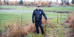 Sala-Heby GK:s greenkeeperTorbjörm Pettersson bredvid en av de stolpar som satts upp för det vildsvinsstaket som just nu sätts upp.